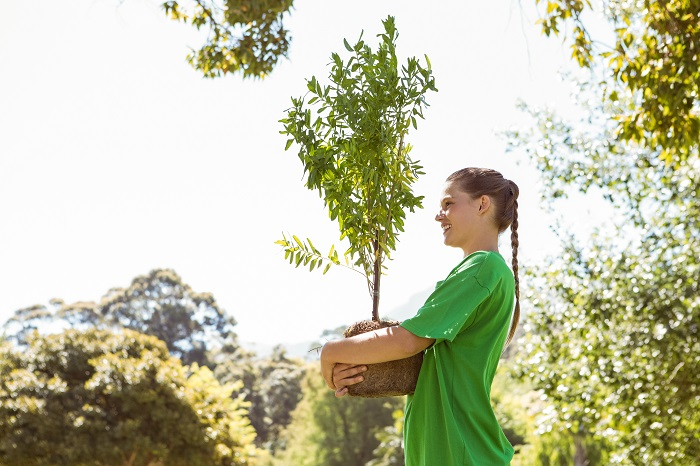 woman holding a young tree to promote sustainable future